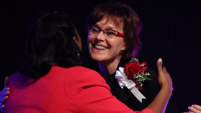 Lynne Maquat is congratulated after she is named the 2014 recipient of the Athena Award.