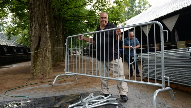 """Juan Dominguez moves a barricade in preparation for Triple Crown winner American Pharoah at Saratoga Race Course, Tuesday, Aug. 25, 2015, in Saratoga Springs, N.Y. Trainer Bob Baffert says American Pharoah """"looks great"""" two days before the horse is scheduled to leave California and arrive at Saratoga Race Course for Saturday's Travers Stakes. (Patrick Dodson/The Daily Gazette via AP)  TROY, SCHENECTADY; SARATOGA SPRINGS; ALBANY AND AMSTERDAM OUT; MANDATORY CREDIT"""