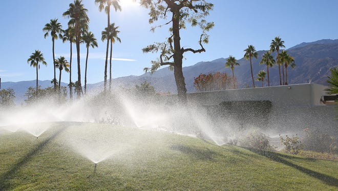 Sprinklers spray the grass at Greenhouse West Condos in Palm Springs on Dec. 17, 2015.