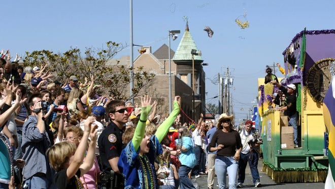 BILOXI, MS - FEBRUARY 28:  Residents line the streets as Mardi Gras beads and trinkets fly through the air while floats pass by for the annual Mardi Gras parade on Fat Tuesday February 28, 2006 in Biloxi, Mississippi. (Photo by Marianne Todd/Getty Images)