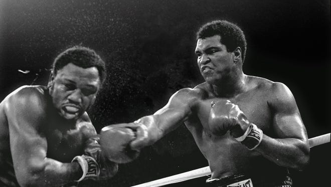 In this Oct. 1, 1975 file photo, spray flies from the head of challenger Joe Frazier, left, as heavyweight champion Muhammad Ali connects with a right in the ninth round of their title fight in Manila, Philippines.