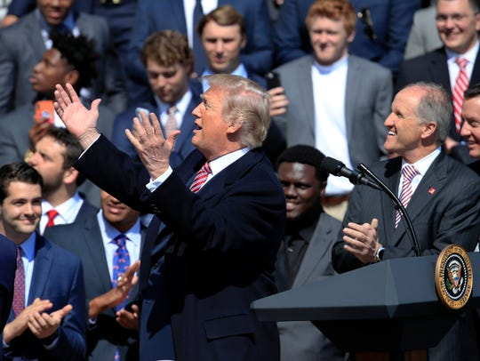 President Donald Trump gestures as he acknowledges