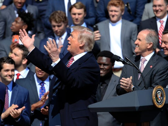 President Donald Trump gestures as he acknowledges some team members during a ceremony to honor the 2017 NCAA football national champions, the Alabama Crimson Tide on the White House's South Lawn, in Washington, Tuesday, April 10, 2018. (AP Photo/Manuel Balce Ceneta)