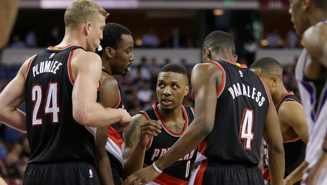 Portland Trail Blazers players, from left, Mason Plumlee, Al-Farouq Aminu, Damian Lillard, Maurice Harkless and C.J. McCollum, huddle during a timeout in the first quarter of an NBA basketball game against the Sacramento Kings on Tuesday, April 5, 2016, in Sacramento, Calif.