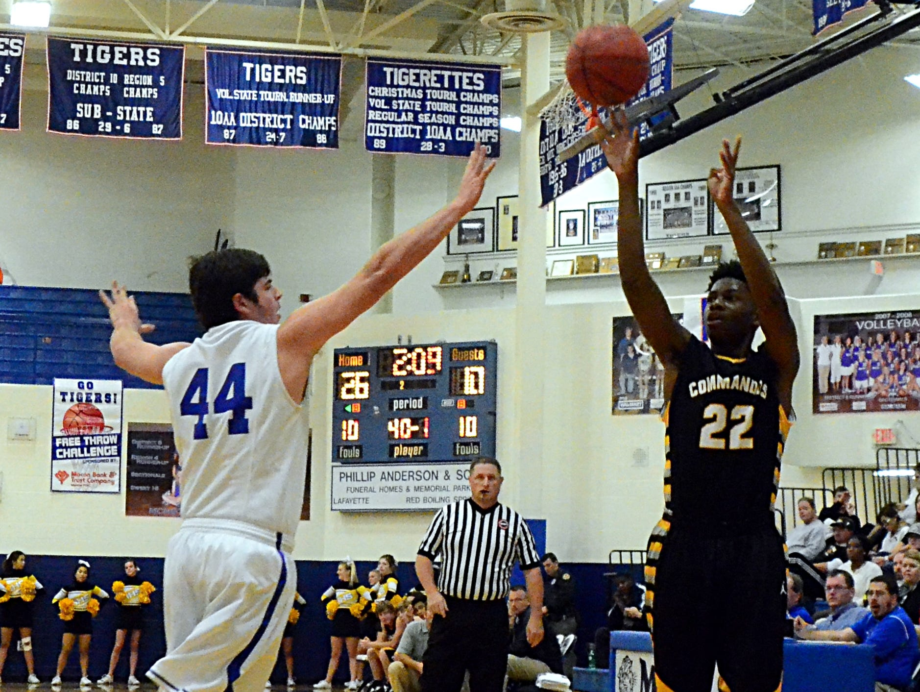 Hendersonville High senior Bryan Scott releases a 3-pointer as Macon County senior Clay Carnahan challenges during second-quarter action.