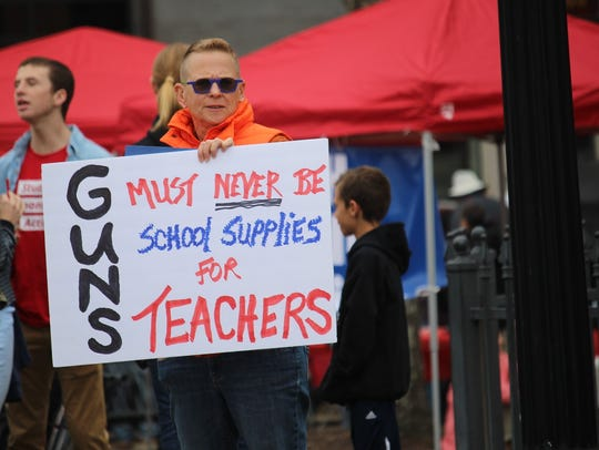 Retired teacher Robin White holds a sign Saturday at