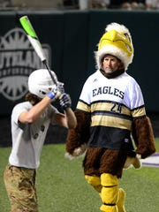 Abilene High coach Ryan Lewis, dressed as the Eagle mascot, walks across to the Cooper dugout, while Cooper's Josh Martin (soldier) takes practice swings during a costume scrimmage Monday at Abilene Christian University's Crutcher Scott Field.