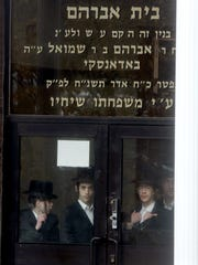 Students stand at the entrance of  a yeshiva in the