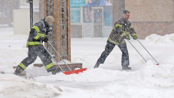 Mandan firefighters Shane Weltikol, left, and Chad Nicklos clear accumulating snow from outside the firehouse in downtown Mandan, N.D., as the Christmas Day blizzard intensifies on Sunday, Dec. 25, 2016. Most of the Dakotas and southwest Minnesota had turned into a slippery mess due to freezing rain Sunday morning before snow arrived later in the day as temperatures fell.