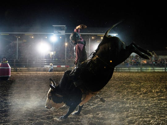 A competitor rides a bull during a rodeo in Woodstock, Virginia, last year.