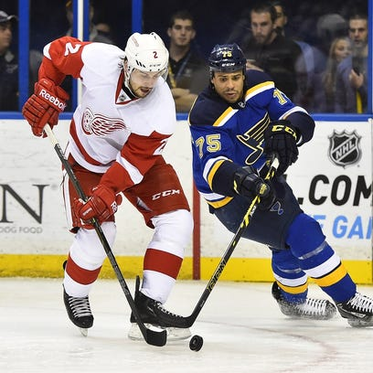 St. Louis Blues right wing Ryan Reaves and Detroit Red Wings defenseman Brendan Smith, left, battle for the puck Jan. 15, 2015.