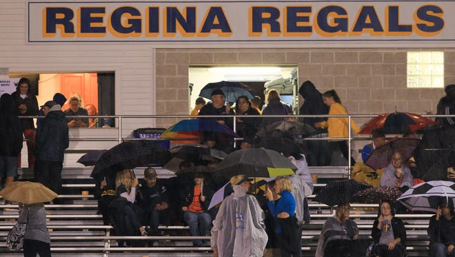 Regina fans take shelter following multiple lightning delays before the Regals' scheduled home game against Solon on Friday. The game is postponed to 7 p.m. Saturday.