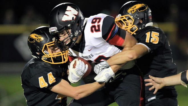 Mid-Prairie's Paul Hawbaker (44) and Blake Schwartz (15) tackle Williamsburg's Ben Subbert during their game in Wellman on Friday, Oct. 2, 2015.