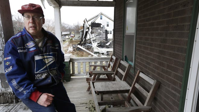 Richard Brown, 60, a retired postal worker, sits on the porch of the house that he has lived in for 57 years on Cabot Street in southwest Detroit. Brown is frustrated with the city's slow response to the abandoned and vacant houses that surround his home.