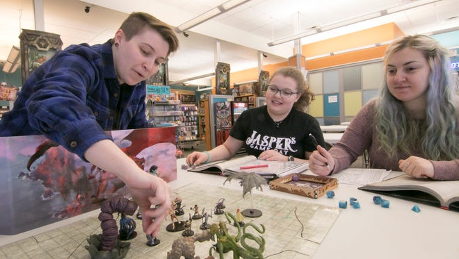 "Jessie Swinton, left, and Sarah Allen, right, co-owners of Ziege Games set up a game of Dungeons & Dragons with Fenway Jones Tuesday, April 17, 2018, at the Hartland Township store. Jones is organizing a fundraising event entitled ""Jasper's Game Day"" to benefit suicide prevention."