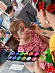 Lillian Lieberman, 6, gets her face painted by Angela