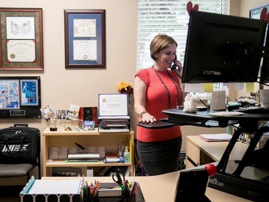 Jessica Walker and many other employees often work from their stand-up desks at Markham Norton Mosteller Wright & Company in Fort Myers.