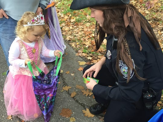 Port Huron Police officer and pirate Patrick Eash hands out candy to a princess during Saturday's Halloween Stroll.