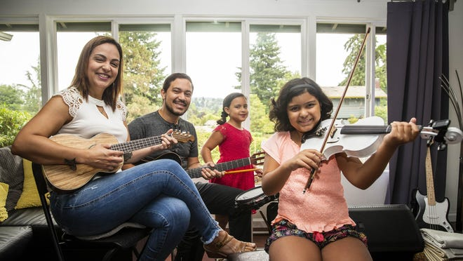 Mariana De Paula and her husband, Beto Silva, are musicians, and they are teaching their two daughters, Lisa, 10, and Nicole, 8, to sing and play instruments. Every two weeks they have a live performance on YouTube. [Dana Sparks/The Register-Guard] - registerguard.com