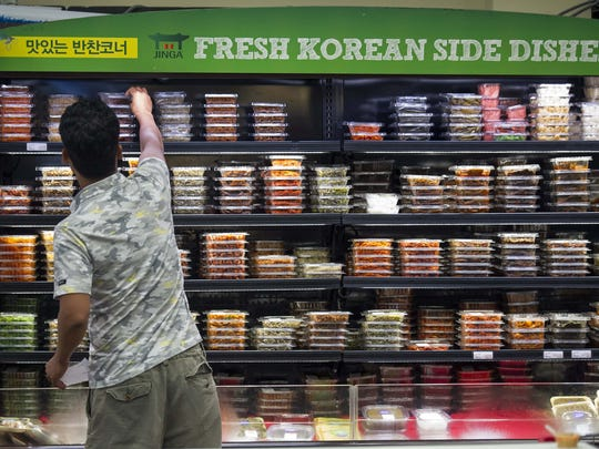 A man reaches for a prepared food item in a refrigerated