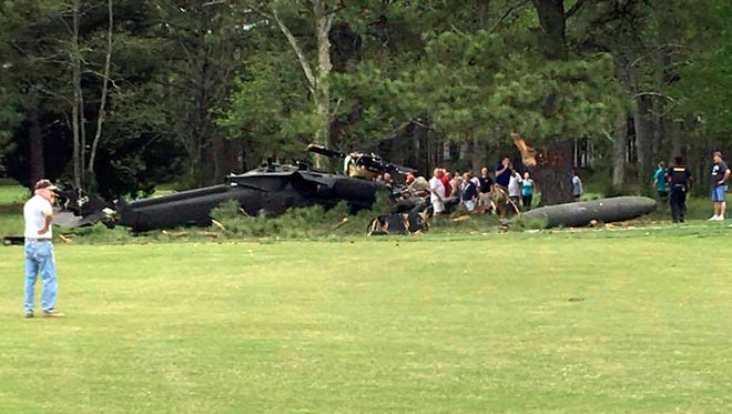 People examine an Army UH-60 helicopter from Fort Belvoir, Virginia, after it crashed at the Breton Bay Golf and Country Club after Monday, April 17, 2017, in Leonardtown, Maryland. Capt. Terikazu Onoda, a 2009 West Point graduate and Irvington, New York, native, was among the soldiers injured.