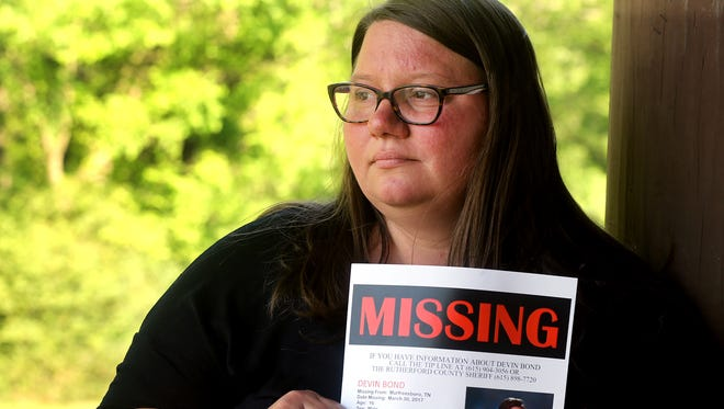 Heather Simmers holds one of the many posters about her missing son Devin Bond, on Wednesday, April 26, 2017, who has been missing for nearly a month.