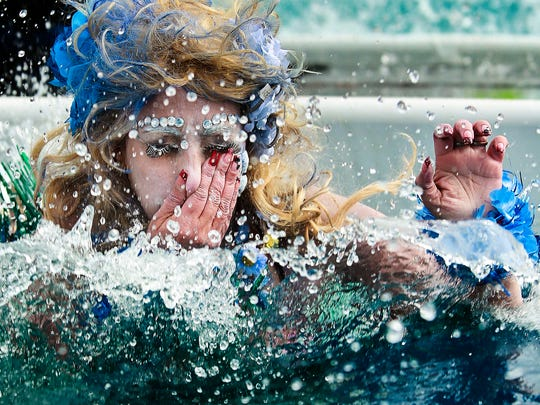 A participant in the 17th annual Louisville Polar Plunge fundraiser event holds her nose as she hits the chilly water on February 28, 2015. 