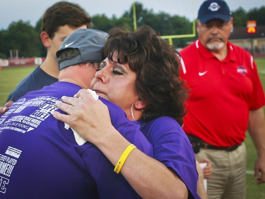 Melanie Loupe hugs Siegel High School Principal Larry Creasy at the end of a ceremony honoring her late son at Oakland High School Friday night.