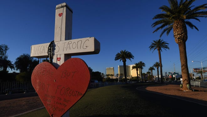 A solitary cross remains at a memorial site in front of the Mandalay Hotel (back) for the 58 victims of the worst shooting in modern U.S. history, in Las Vegas, Nevada on Nov.15, 2017.