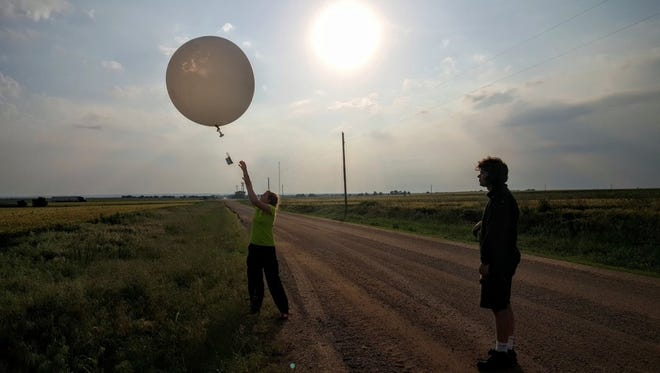 CSU graduate students Stacey Hitchcock and Greg Herman launch a weather balloon near sunset in Kansas as part of a massive research project to help understand how thunderstorms form at night.