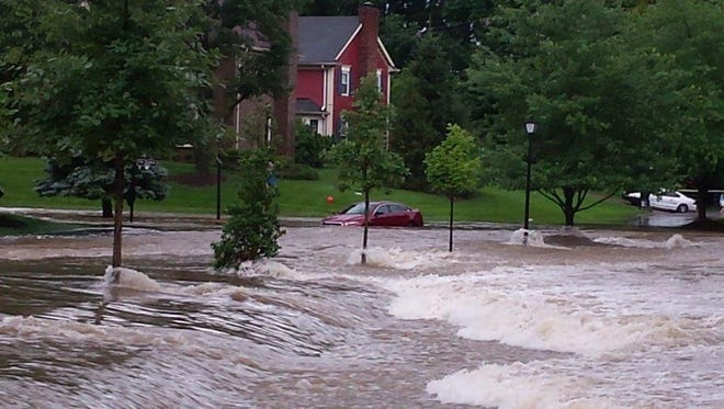 Water rushes along Colonel Anderson Parkway at South Lyndon Lane during recent flooding in Hurstbourne.