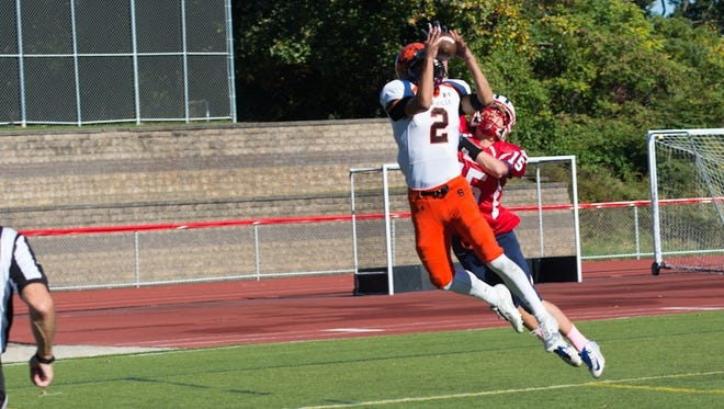 Somerville's Chris Criempola catches a pass while being defended by Governor Livingston's Matt Pacheco during Saturday's game.