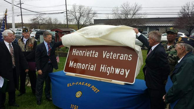 Sen. Patrick Gallivan, left, and Allan Richards of Assembly member Harry Bronson's office join local veterans in unveiling a sign dedicating the Henrietta Veterans Memorial Highway.