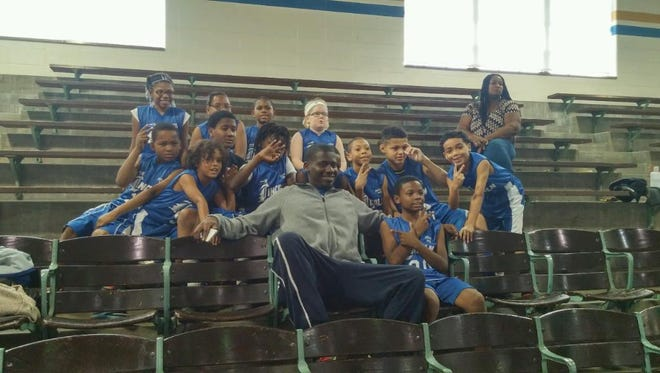 Lincoln Elementary Basketball Coach Jordan Cain poses with the team before a Nov. 7 scrimmage.
