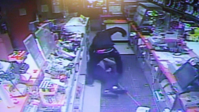 Here is a surveillance photo showing a suspect beating an elderly attendant at the Community Market on Trinity Lane.
