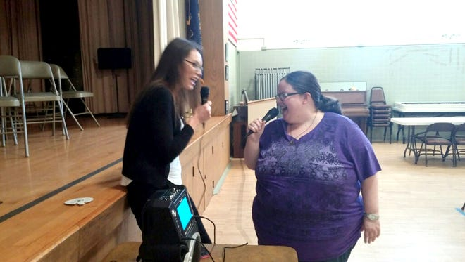 Compeer client Amanda Knepp, right, alongside her friend, Stacy Griffiths, sing karaoke at a social event held at the Lebanon County Area Agency on Aging building in Lebanon.