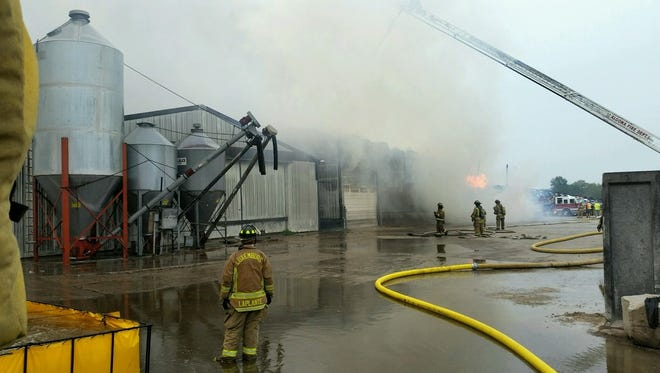 Firefighters from multiple Kewaunee, Door and Manitowoc county departments fight a blaze in a hay shed at Ebert Enterprises on Thursday afternoon.
