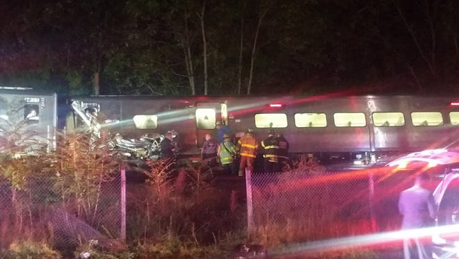 In this photo provided by Sarah Qamar rescue personnel look at a Long Island Railroad train that derailed near New Hyde Park, N.Y., Saturday, Oct. 8, 2016. The commuter train derailed east of New York City after it hit a work train on the tracks. A spokesman for the Long Island Rail Road says the eastbound train derailed east of New Hyde Park just after 9 p.m. Saturday.