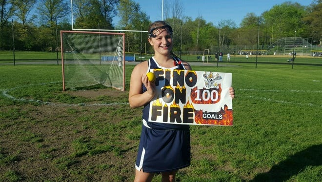 Highland lacrosse player Eliz Fino poses with a poster and commemorative game ball after scoring her 100th career goal.