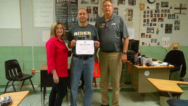 Sonja Gandy of the Major Francis Grice Chapter of the Daughters of the American Revolution presents a certificate to the Outstanding Teacher of the Year, Todd Chamberlain.  Pictured from left are Sonja Gandy; Todd Chamberlain, history teacher and coach at Rider High School; and Rider Principal Dee Palmore.