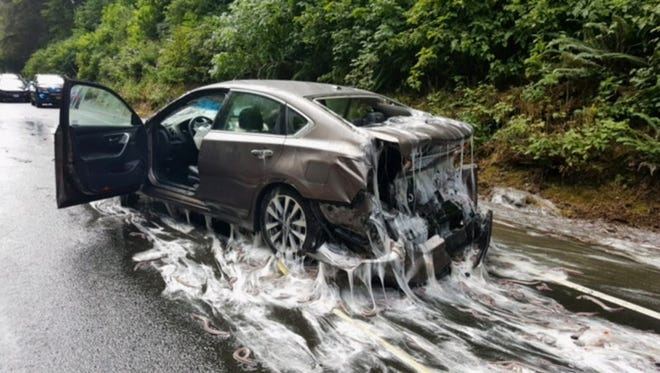 This photo provided by the Oregon State Police shows a vehicle after a truck overturned and its container with eels hit the vehicle on Highway 101 in Depoe Bay, Ore., July 13, 2017.