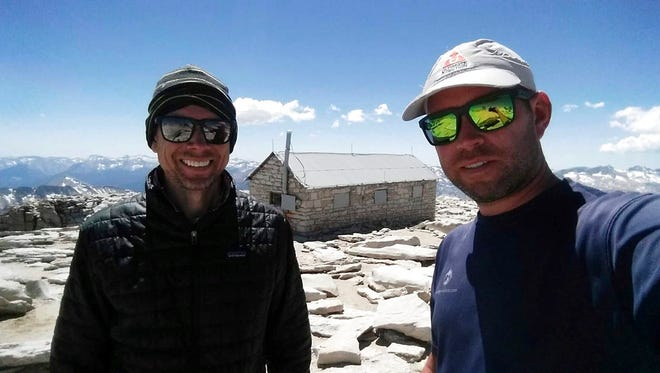 In this August 2017 photo provided by Brian McKinney, Sam Vonderheide, right, and McKinney, left, pose for a photo on the top of Mount Whitney, Calif. The two hikers walking a High Sierra trail videotaped a nerve-wracking stare-down with a wild mountain lion on July 23.