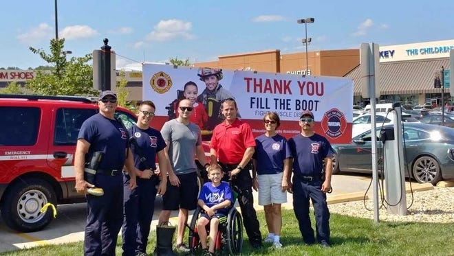 Branson firefighters raised $16,000 for the Muscular Dystrophy Association. Engineer Darryll Hembree, far left, firefighter Brett Mitrenga, Captain Josh Boehm, Division Chief Randy Fogle, administrative assistant Janice Denega, and firefighter Jerry Whitworth are pictured with 8-year-old MDA Goodwill Ambassador DJ Everett from Seymour, Mo.