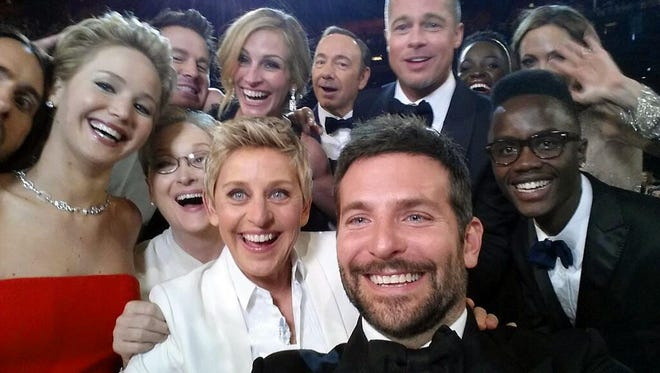 """This image released by Ellen DeGeneres shows actors front row from left, Jared Leto, Jennifer Lawrence, Meryl Streep, Ellen DeGeneres, Bradley Cooper, Peter Nyongío Jr., and, second row, from left, Channing Tatum, Julia Roberts, Kevin Spacey, Brad Pitt, Lupita Nyongío and Angelina Jolie as they pose for a """"selfie"""" portrait on a cell phone during the Oscars at the Dolby Theatre on Sunday, March 2, 2014, in Los Angeles. (AP Photo/Ellen DeGeneres) ORG XMIT: NYET600"""