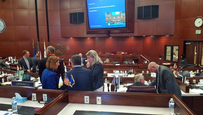 In this Oct. 11, 2016, file photo, Republican lawmakers huddle as they discuss a bill that would authorize public funds for an NFL stadium and convention center expansion in Las Vegas during a special legislative session in Carson City, Nev. State lawmakers around the country have introduced and supported policies that help their own businesses, their employers and sometimes their personal finances, according to an analysis of financial disclosure forms and legislative votes by the Center for Public Integrity and The Associated Press.