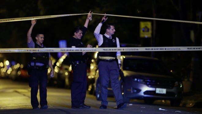 In this Sept. 2, 2017, file photo, police lift crime scene tape after two people were shot and transported to Stroger Hospital in Chicago. Chicago ended 2017 with fewer homicides than the year before but raging gang wars in the city's most violent neighborhoods drove the total beyond the 600 mark for just the second time in well over a decade. (John J. Kim/Chicago Tribune via AP, File) ORG XMIT: ILCHT301