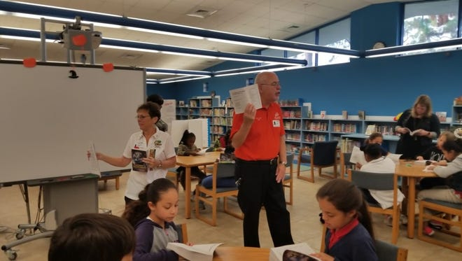 Vero Beach Elks Exalted Ruler Paul Diaz, right, with Pat Diaz give third-grade students an overview of their new dictionary.