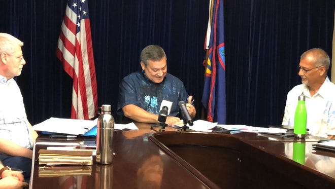 In this July 13, 2018 file photo, Gov. Eddie Calvo vetoes the bill repealing the 2 percent sales tax, which was projected to bring in about $120 million in fiscal 2019. Days later, senators overrode the veto.