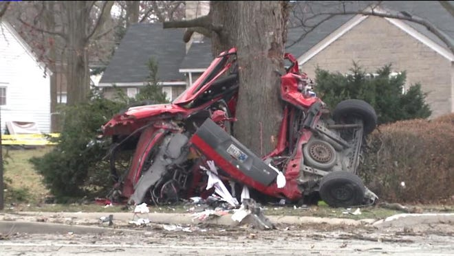 Wreckage from a car is wrapped around a tree near 38th and Denny streets on Friday. The driver was killed, police say,.