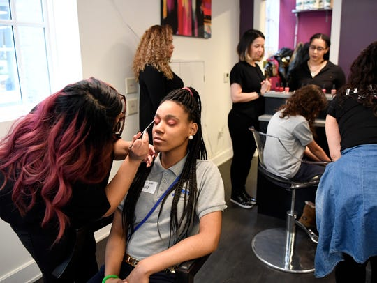 """Fajr McCray, 15, gets her makeup done by Sharon Calixto, a student at the Paul Mitchell school at Hair491 in Montclair, NJ on Wednesday, April 11, 2018. The event, called """"Something Wonderful,"""" is run by Jazz House Kids and provides a day of pampering at Hair491 with food and music for students from John F. Kennedy School in Newark."""